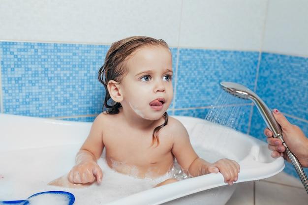 Kleines schönes mädchen badet in einem badezimmer, spielt den narren und zeigt zunge.