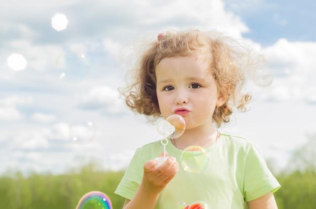 Kleines schönes mädchen bläst seifenblasen. glückliches sommerkind in der natur.