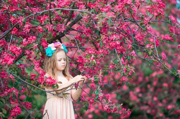 Kleines schönes mädchen, das geruch in einem blühenden frühlingsgarten genießt