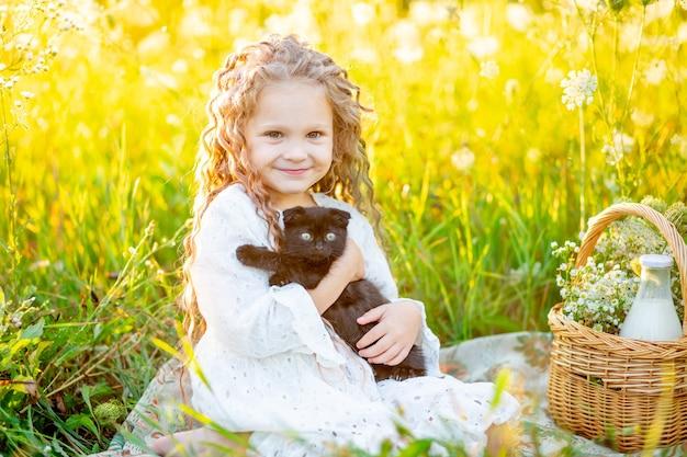 Kleines schönes mädchen, das im sommer auf dem rasen mit einem schwarzen kätzchen sitzt