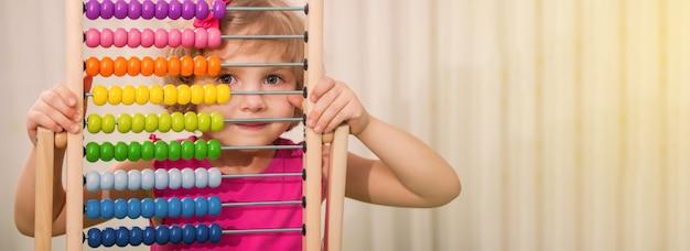 Kleines schönes mädchen, das mehrfarbigen abakus in ihren händen hält. vorschulkind mit hellen lernspielzeugen. bildung
