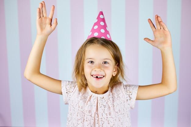 Kleines schönes mädchen, das rosa kappe des geburtstages auf rosa weißer streifenwand trägt, die mit glücklichem gesicht lächelt. alles gute zum geburtstag.