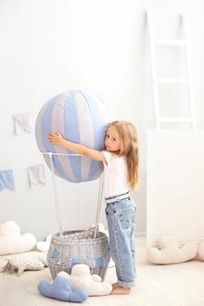Kleines schönes mädchen in der zufälligen kleidung steht von einem dekorativen ballon. das kind spielt im kinderzimmer.