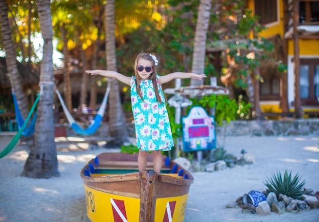 Kleines schönes mädchen in einem boot auf dem strand am exotischen erholungsort