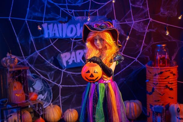 Kleines schönes mädchen in einem hexenkostüm feiert glückliche halloween-partei im inneren mit kürbissen.