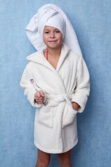 Kleines schönes mädchen in einem weißen bademantel