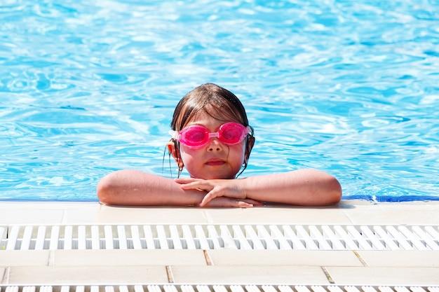 Kleines schönes mädchen in rosa wassergläsern im pool