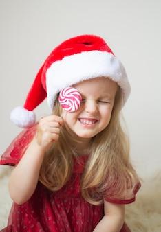 Kleines schönes mädchen in santa hat red party dress warteweihnachten