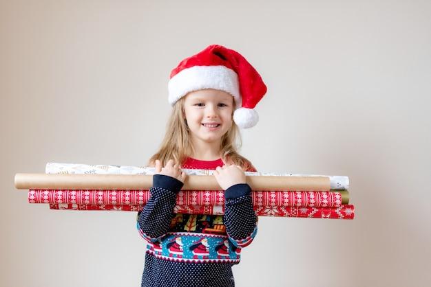 Kleines schönes mädchen in santa red hat mit dem packpapier, das auf weihnachten und das neue innenjahr glücklich wartet