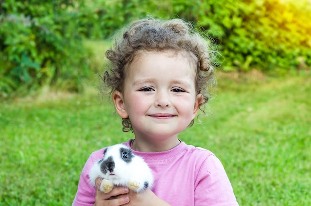 Kleines schönes mädchen lächelnd, ein babykaninchen auf dem grünen gras umarmend. glücklich lachendes kind und haustier