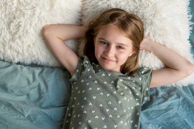 Kleines schönes mädchen mit blonden haaren, das im bett liegt und die kamera im schlafzimmer mit...