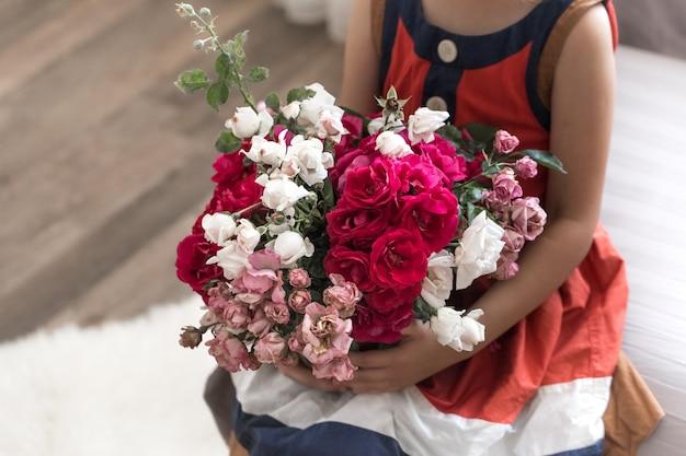 Kleines schönes mädchen mit einem strauß rosen
