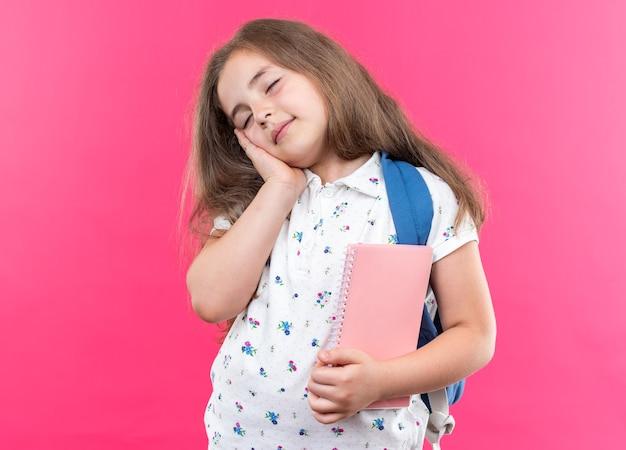 Kleines schönes mädchen mit langen haaren mit rucksack, das ein notizbuch hält, das die hand auf ihrer wange hält und mit geschlossenen augen lächelt, die über rosafarbener wand stehen?