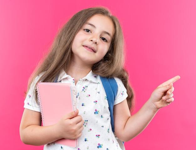 Kleines schönes mädchen mit langen haaren mit rucksack, das ein notizbuch hält, das fröhlich lächelt und mit dem zeigefinger auf die seite zeigt, die auf rosa steht