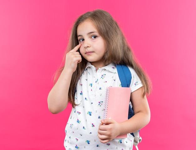 Kleines schönes mädchen mit langen haaren mit rucksack, das ein notizbuch hält, das mit dem zeigefinger auf ihr auge zeigt und nach vorne schaut, mit ernstem gesicht über rosa wand stehend Premium Fotos