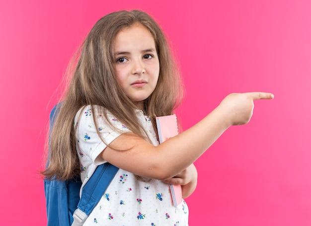 Kleines schönes mädchen mit langen haaren mit rucksack, das ein notizbuch hält, das mit dem zeigefinger zur seite zeigt und nach vorne schaut, mit ernstem gesicht, das über rosa wand steht