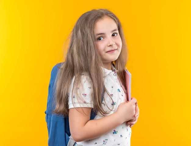 Kleines schönes mädchen mit langen haaren mit rucksack, das ein notizbuch hält, das mit glücklichem gesicht lächelt, das auf orange steht