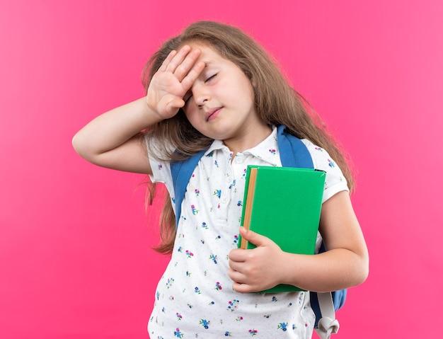Kleines schönes mädchen mit langen haaren mit rucksack, das ein notizbuch hält, das müde und gelangweilt aussieht und die hand auf ihrer stirn hält, die über einer rosa wand steht