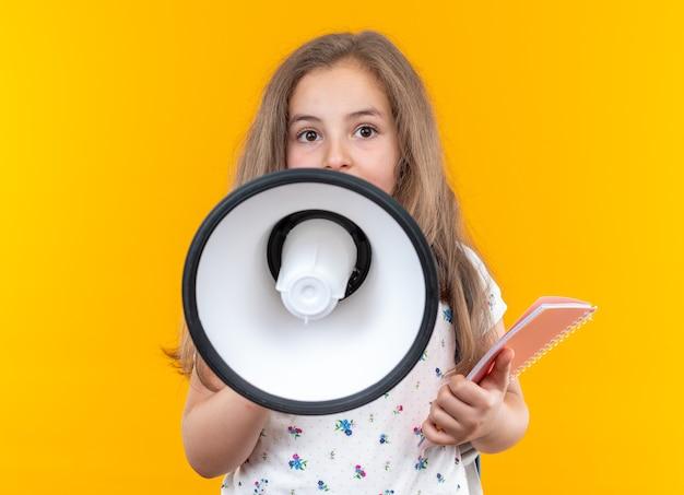 Kleines schönes mädchen mit langen haaren mit rucksack, das ein notizbuch hält, das zum megaphon schreit, das auf orange steht