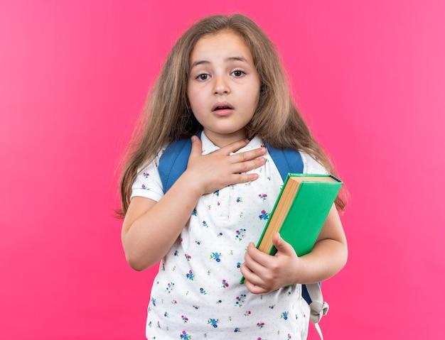 Kleines schönes mädchen mit langen haaren mit rucksack, das ein notizbuch hält, erstaunt und überrascht, die hand auf ihrer brust zu halten, die auf rosa steht