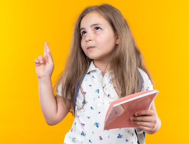 Kleines schönes mädchen mit langen haaren mit rucksack, das ein notizbuch hält und lächelnd mit dem zeigefinger auf etwas zeigt, das über der orangefarbenen wand steht?