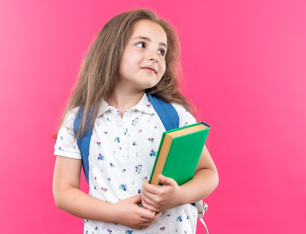Kleines schönes mädchen mit langen haaren mit rucksack, das ein notizbuch hält und mit einem lächeln auf einem glücklichen gesicht, das über einer rosa wand steht, beiseite schaut