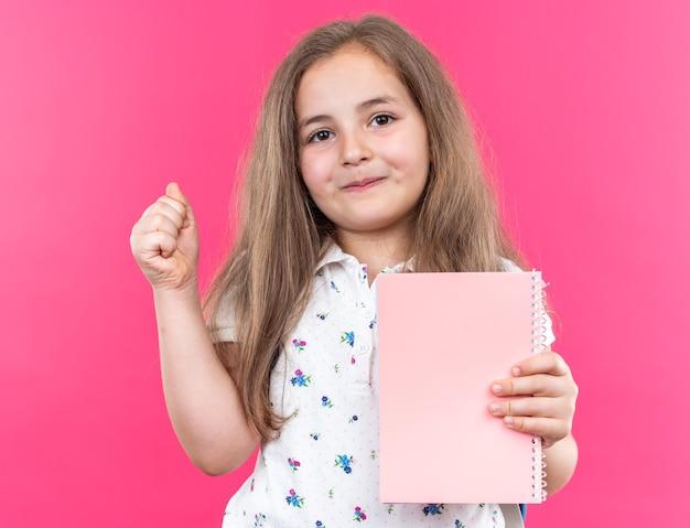 Kleines schönes mädchen mit langen haaren mit rucksack, das ein notizbuch hält und mit einem lächeln auf einem glücklichen gesicht nach vorne schaut, das den daumen über der rosa wand zeigt