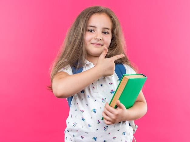 Kleines schönes mädchen mit langen haaren mit rucksack, das ein notizbuch hält und nach vorne schaut, fröhlich lächelt und mit dem zeigefinger auf die seite zeigt, die über rosa wand steht