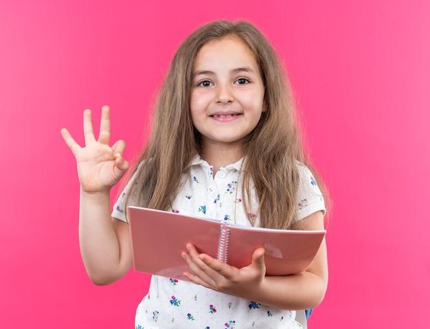 Kleines schönes mädchen mit langen haaren mit rucksack, das ein notizbuch hält und nach vorne schaut, glücklich und positiv, das ok singt und fröhlich über rosa wand steht