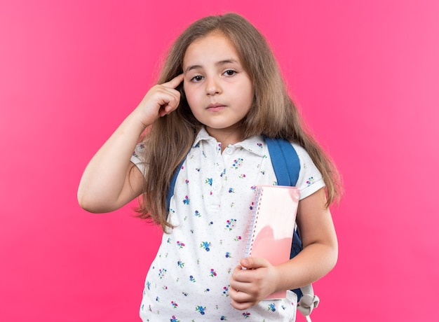 Kleines schönes mädchen mit langen haaren mit rucksack, das ein notizbuch mit ernstem gesicht hält, das mit dem zeigefinger auf ihre schläfe zeigt, die auf rosa steht
