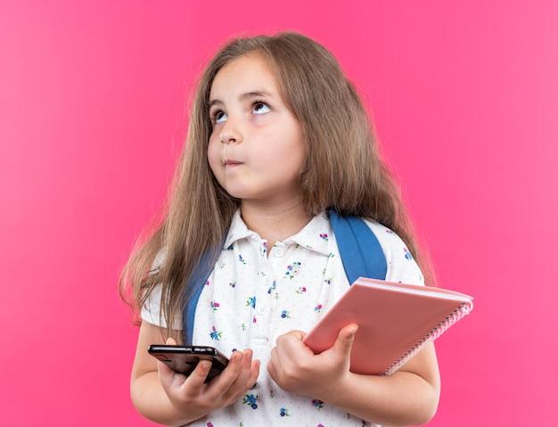 Kleines schönes mädchen mit langen haaren mit rucksack, das notebook und smartphone hält, das verwirrt auf rosa aufschaut