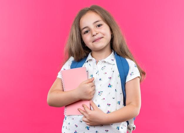 Kleines schönes mädchen mit langen haaren mit rucksack, das notizbuch hält und nach vorne schaut, fröhlich glücklich und positiv über rosa wand stehend lächelt