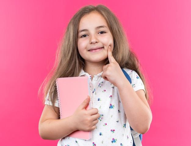 Kleines schönes mädchen mit langen haaren mit rucksack, das notizbuch hält und nach vorne schaut, fröhlich lächelt und den finger auf ihre wange hält, die über rosa wand steht