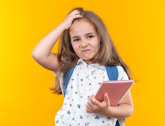 Kleines schönes mädchen mit langen haaren mit rucksack, das notizbuch hält, verwirrt mit der hand auf dem kopf, die auf orange steht