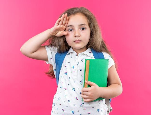 Kleines schönes mädchen mit langen haaren mit rucksack, das notizbuch mit ernstem gesicht hält, das auf rosa steht