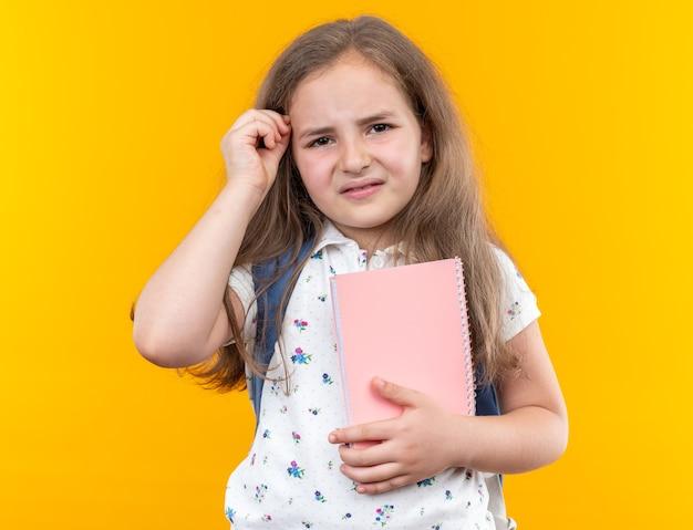 Kleines schönes mädchen mit langen haaren mit rucksack, das notizbuch verwirrt und sehr ängstlich auf orange hält