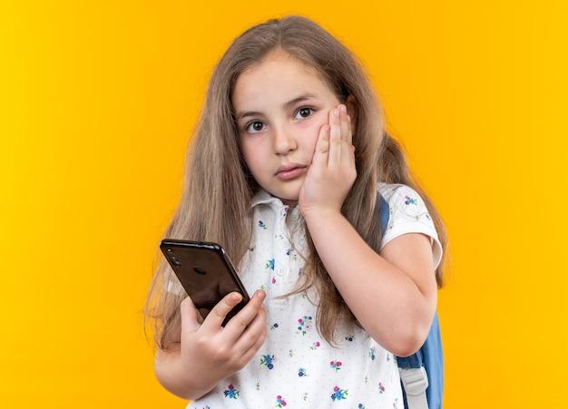 Kleines schönes mädchen mit langen haaren mit rucksack, das smartphone hält, besorgt auf orange stehend