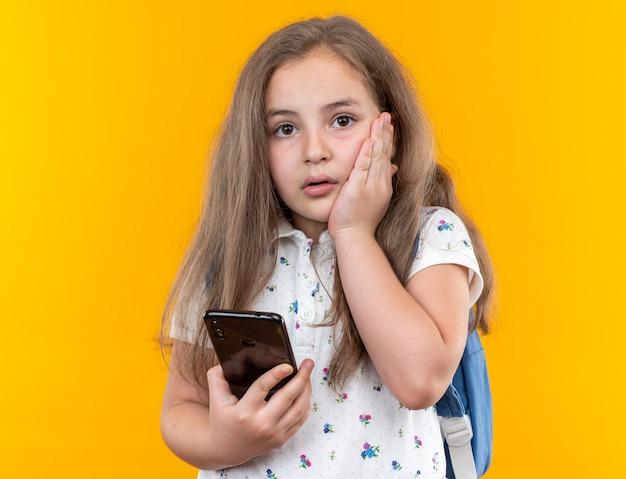Kleines schönes mädchen mit langen haaren mit rucksack, das smartphone hält, das nach vorne schaut, besorgt die hand auf ihrer wange, die über oranger wand steht