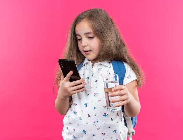 Kleines schönes mädchen mit langen haaren mit rucksack, das smartphone und ein glas wasser hält und selbstbewusst über rosa wand steht