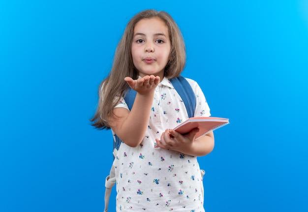 Kleines schönes mädchen mit langen haaren mit rucksack, der ein notizbuch hält und einen kuss bläst, der auf blau steht