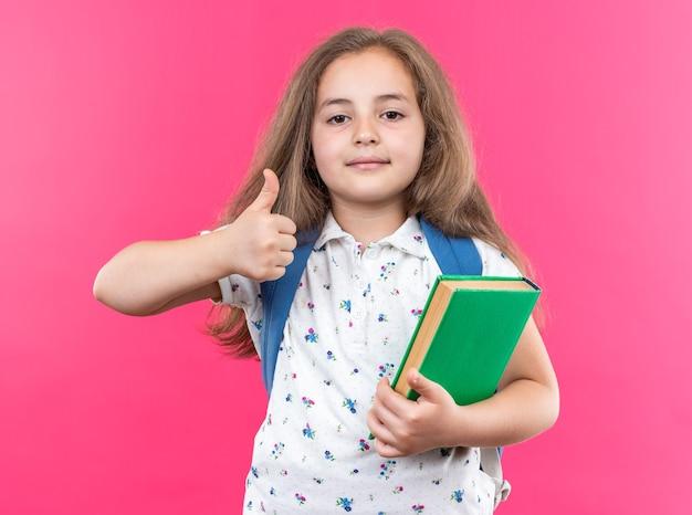 Kleines schönes mädchen mit langen haaren mit rucksack mit notebook, das nach vorne schaut und selbstbewusst lächelt und daumen nach oben über rosa wand steht