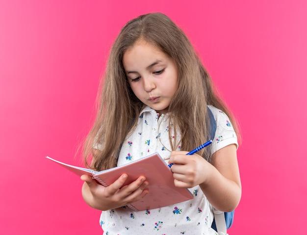 Kleines schönes mädchen mit langen haaren mit rucksack mit notizbuch und stift, der selbstbewusst auf rosa aussieht