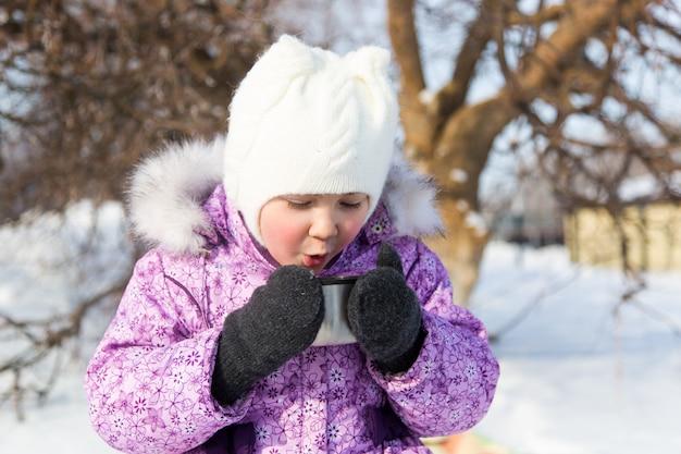 Kleines schönes mädchen trinkt tee in der straße im winter.