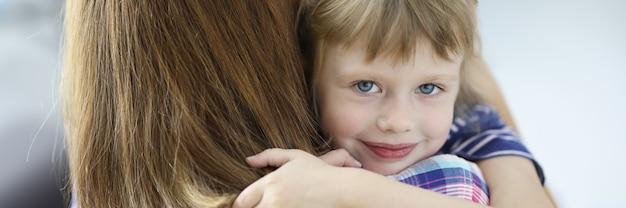 Kleines schönes mädchen umarmt ihre mutter und lächelndes porträt. soziale garantien für frauen mit kindern während des scheidungskonzepts