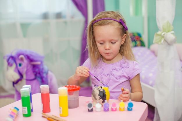 Kleines schönes mädchen zeichnet farben auf dem tisch