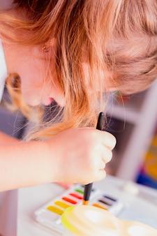 Kleines schönes mädchen zeichnet farben.