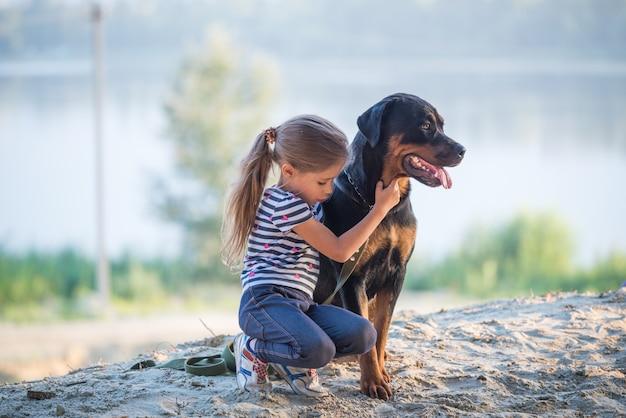 Kleines schönes süßes mädchen und ein großer erwachsener rottweiler-hund, der am rand einer sandigen klippe sitzt, umarmt und einen warmen sommermorgen in einem dichten fichtenwald genießt