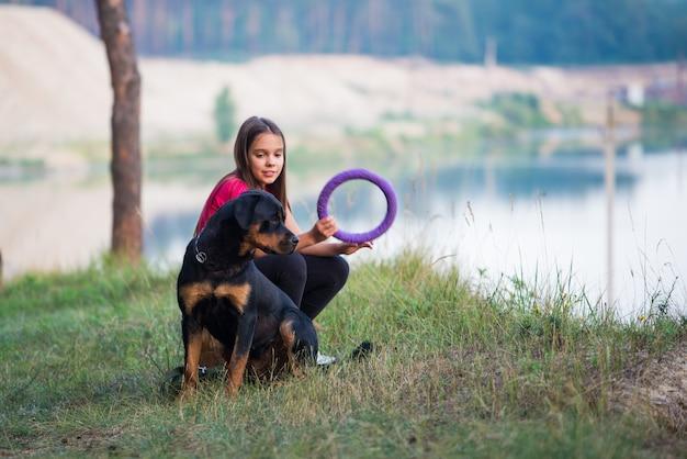Kleines schönes süßes mädchen und großer erwachsener rottweiler-hund, der am rand einer sandigen klippe sitzt, mit einem hundespielzeugring spielt und einen warmen sommermorgen in einem dichten fichtenwald genießt