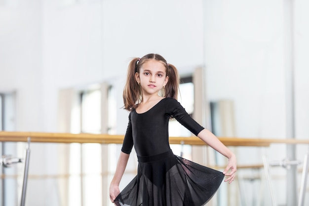 Kleines schönes süßes mädchenkind im studio trainiert für eine tanzstunde.