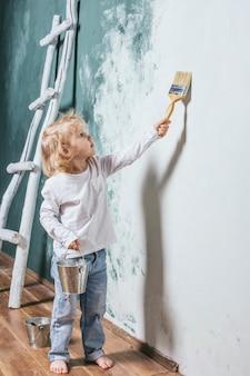 Kleines schönes und glückliches kind in jeans und barfuß malen die wand zu hause mit pinsel